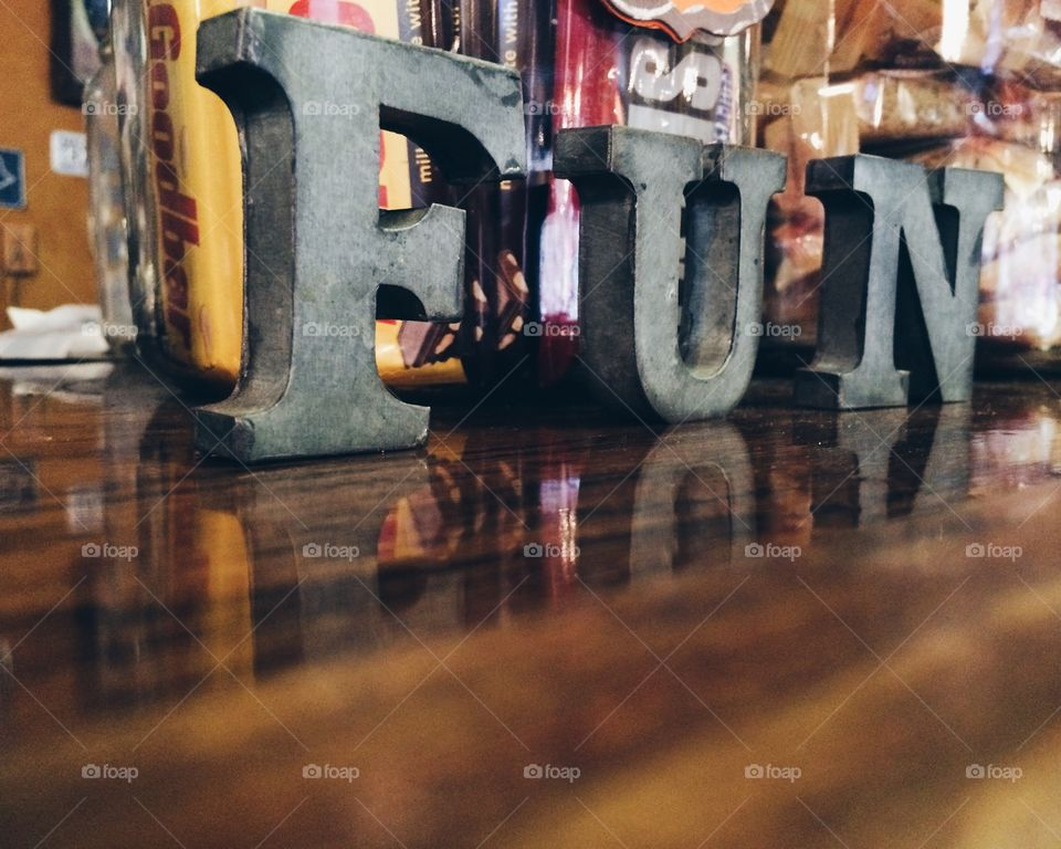 Fun with candy. Fun sign on wooden countertop with candy jars in background.