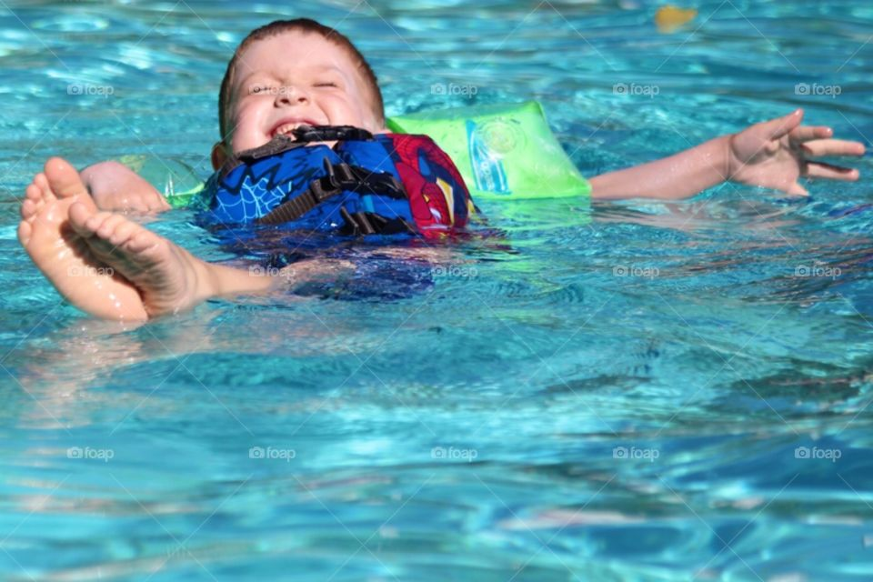 Little boy floating on water in swimming pool