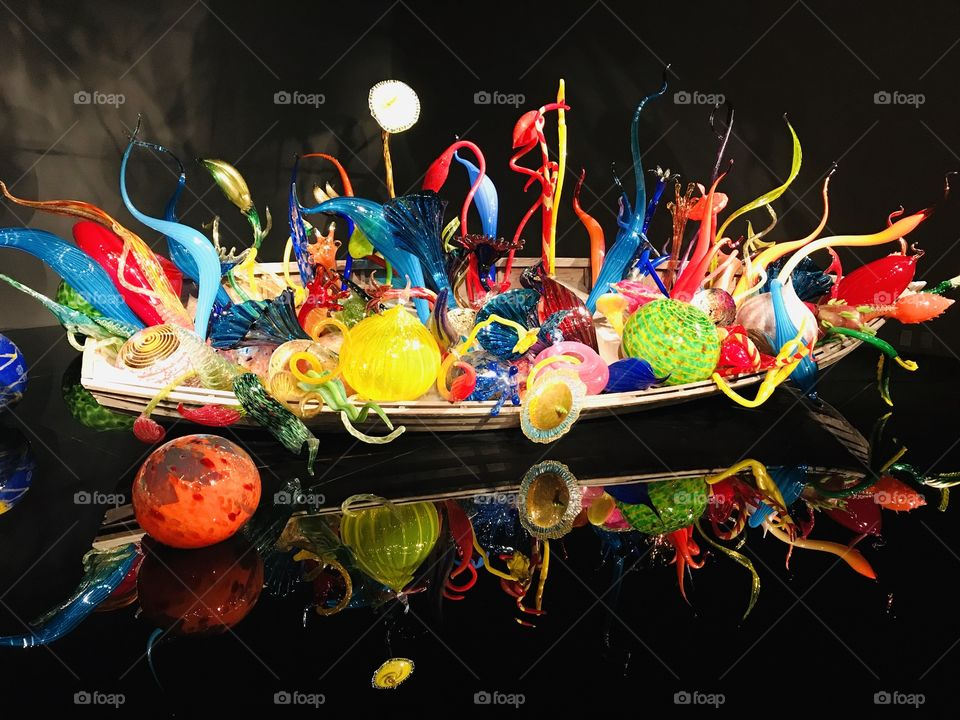 Gorgeous rainbow colored glass balls and ribbons in boat displayed against reflecting black background!