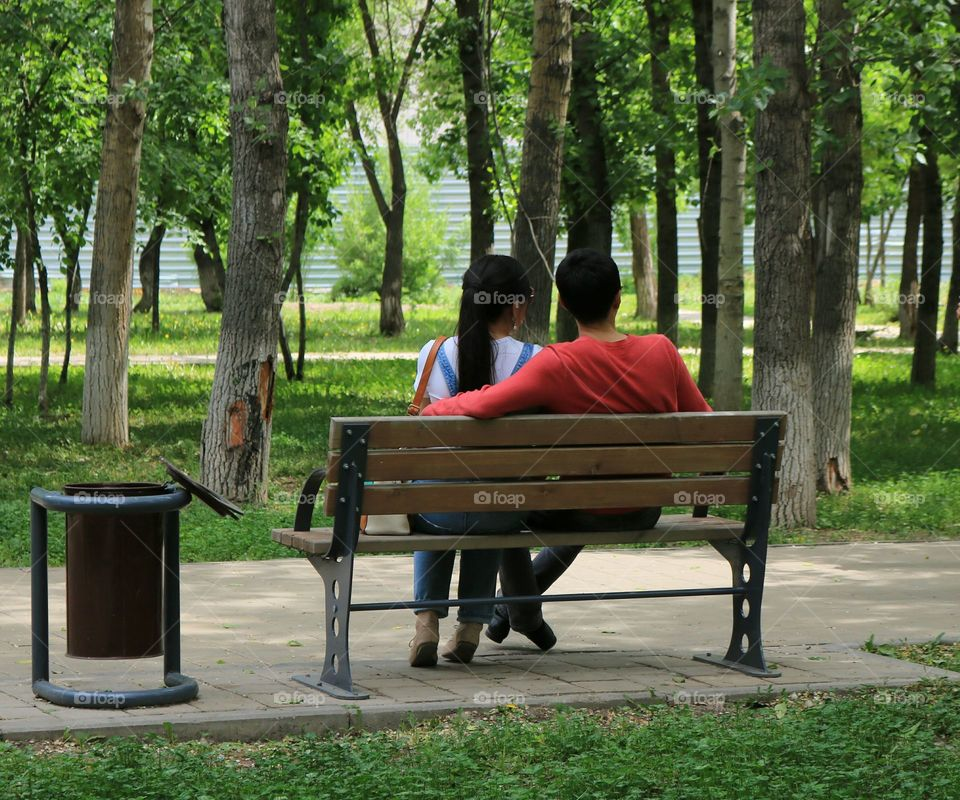 A couple sitting on bench in the park
