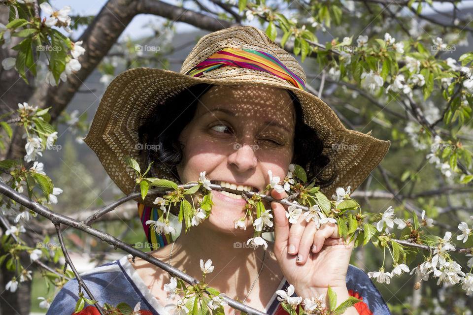 Woman biting tree flowering branch
