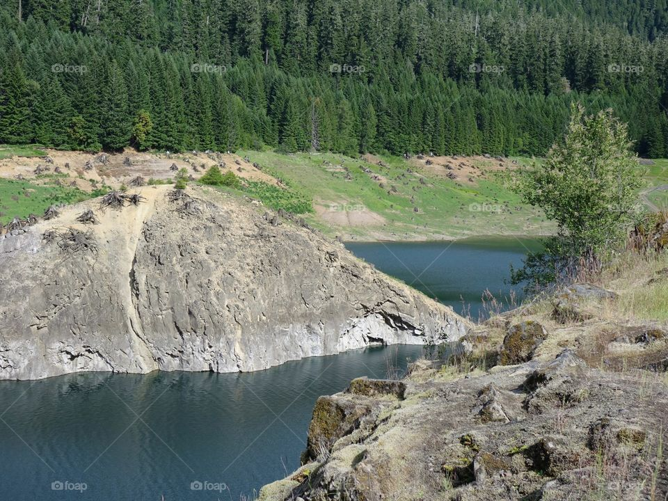 The steep, rocky, and tree covered shores of Cougar Reservoir in Western Oregon on a sunny day.