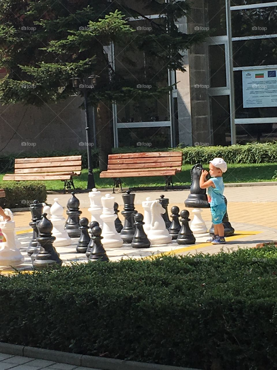 Child playing with chess players on chess board