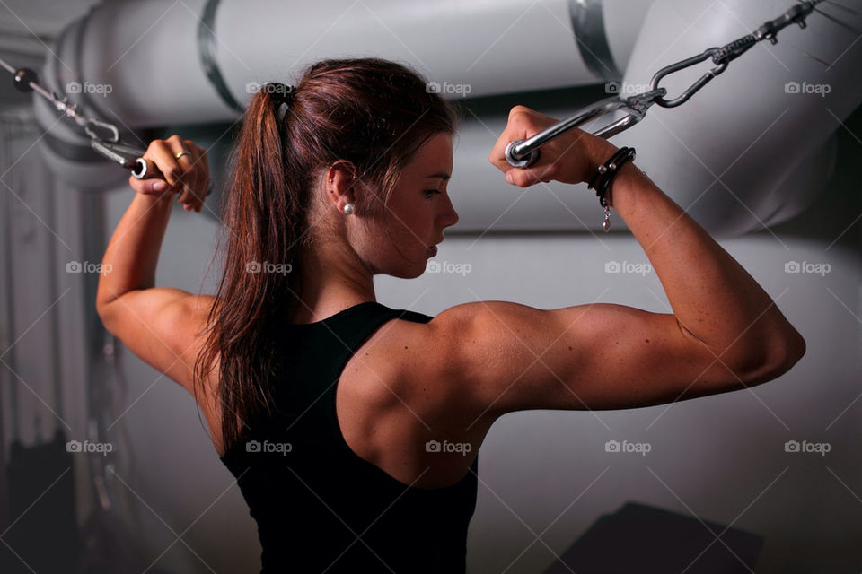 Fit girl doing bicep curls in cablecross