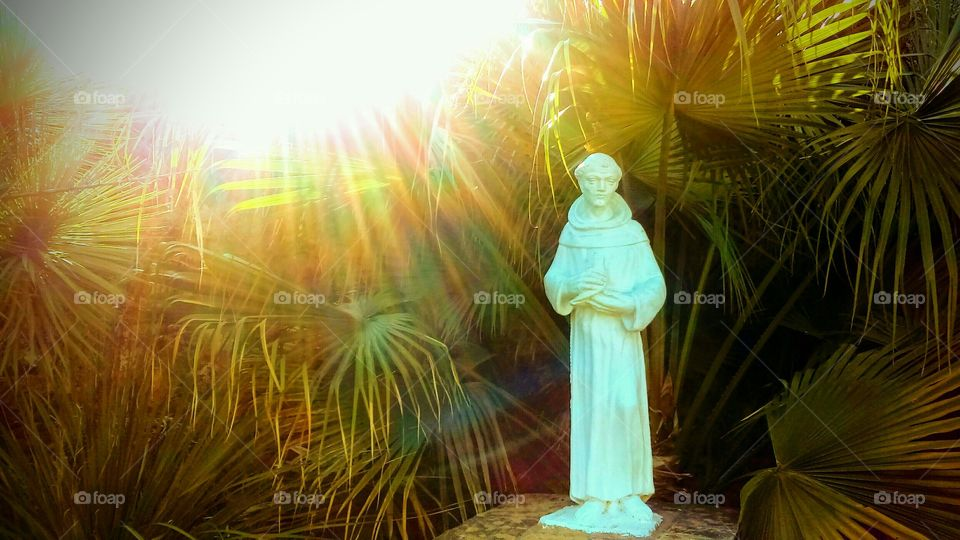 Saint Francis Of Assisi Statuewith sun rays shining down on him at sunset