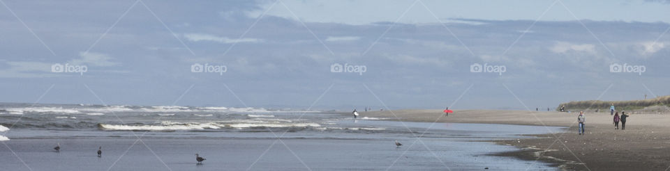 City Beach at Ocean Shores Washington. Mid afternoon crowd. Two surfers heading in shore after a full day of surfing.