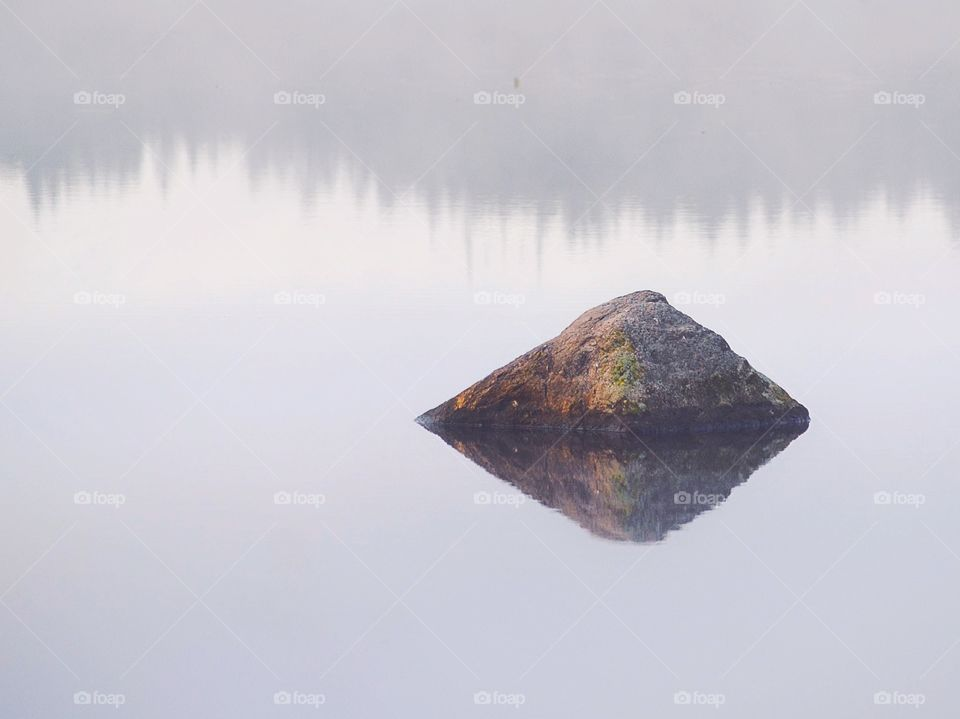 Stone in the foggy lake