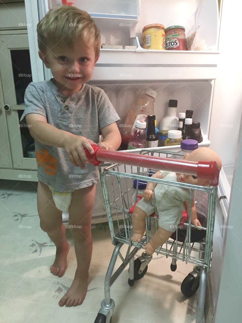 Little boy taking his baby shopping out of the refrigerator.