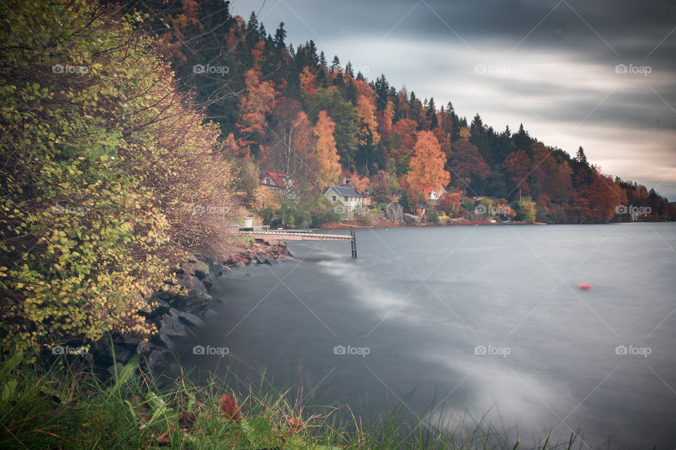 autumn foliage along the shoreline, spotted with tiny cottages in the Swedish countryside
