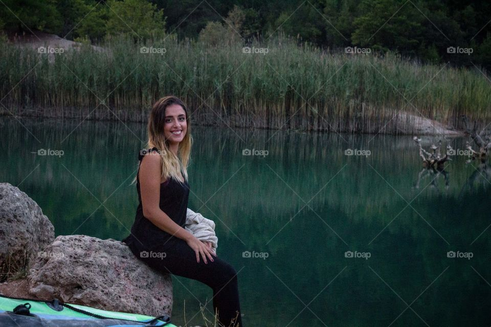 beautiful gild poses near a green lake sitting on a rock and smiling