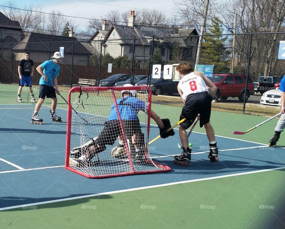 boys playing hockey on tennis court