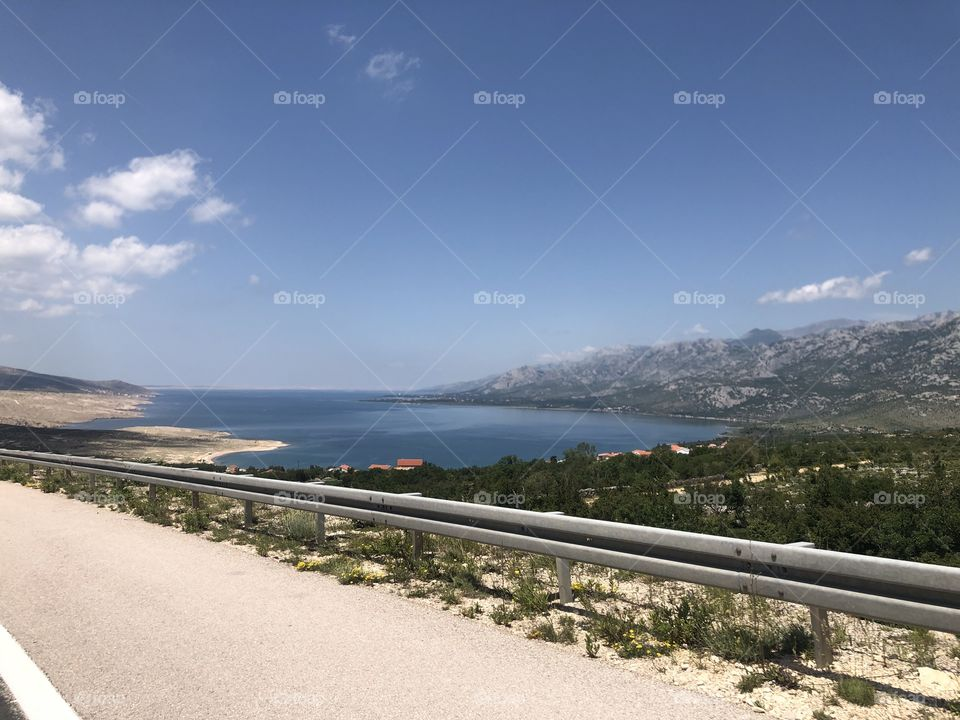 A road going through beautiful views of a lake in the distance large breathtaking mountain views