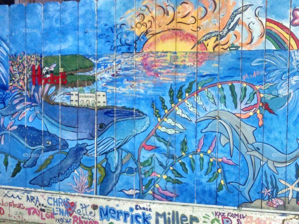 Sunset Cliffs Gas Station mural w/graffiti tags along the base