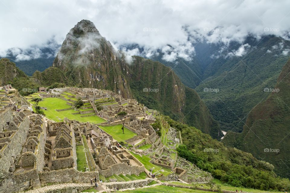 View towards Machu Picchu. View towards famous Machu Picchu. Deep valley on the right hand side. Ruins on the left hand side. Cloudy sky