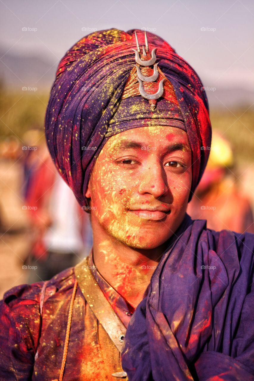 Man in traditional Indian turban smeared with holi colors