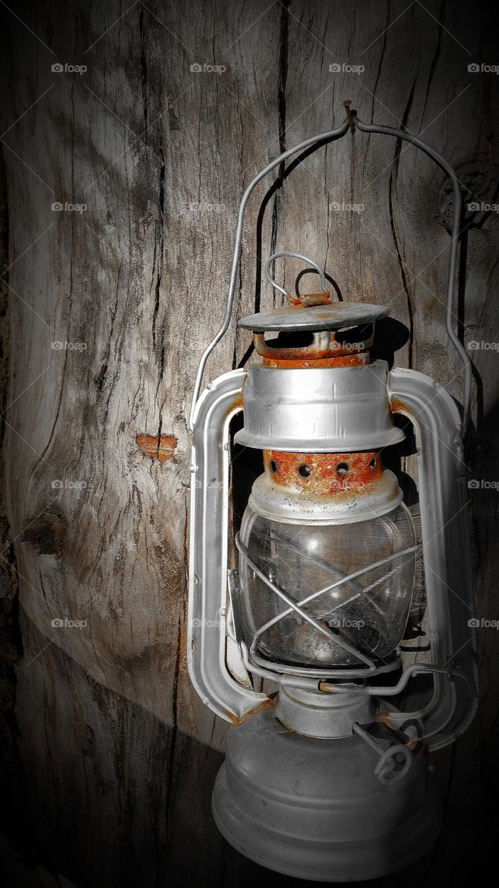 Old lamp hanging on wooden wall