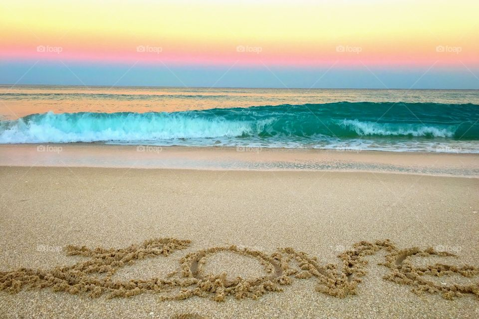 Love text on sand and waves