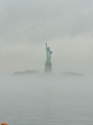 Lady Liberty . Statue of Liberty through the fog in New York City from the Staten Island Ferry