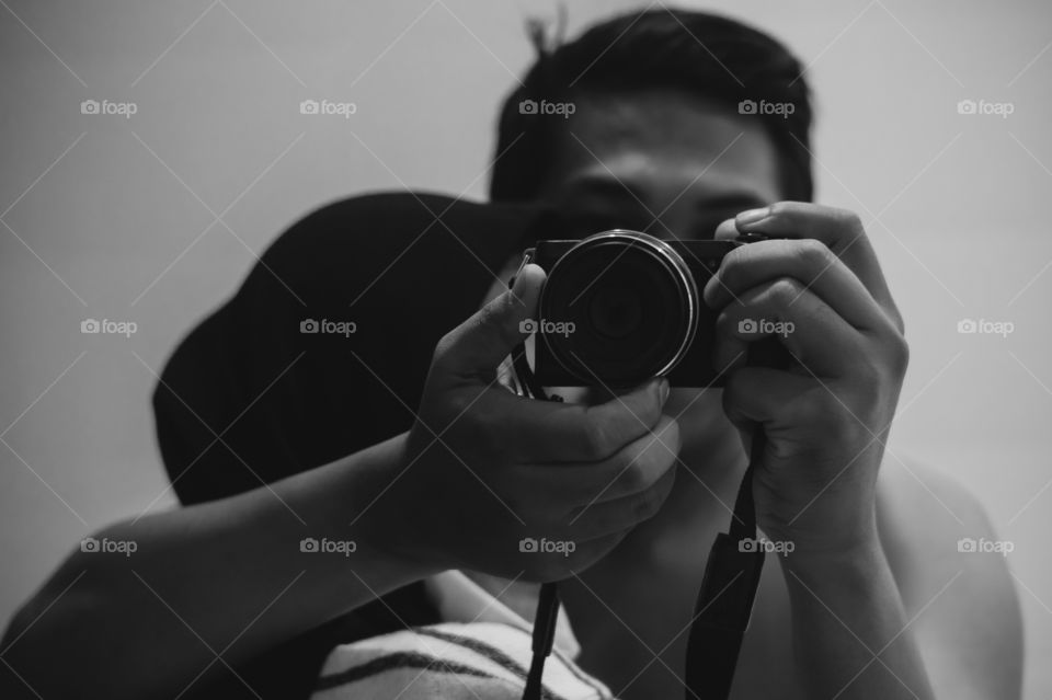 A couple of lovers are hugging in front of a mirror while taking photos