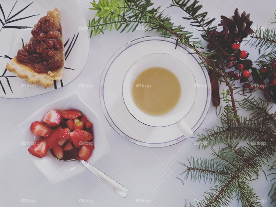 Cup of mint tea, bowl of strawberries and pecan pie