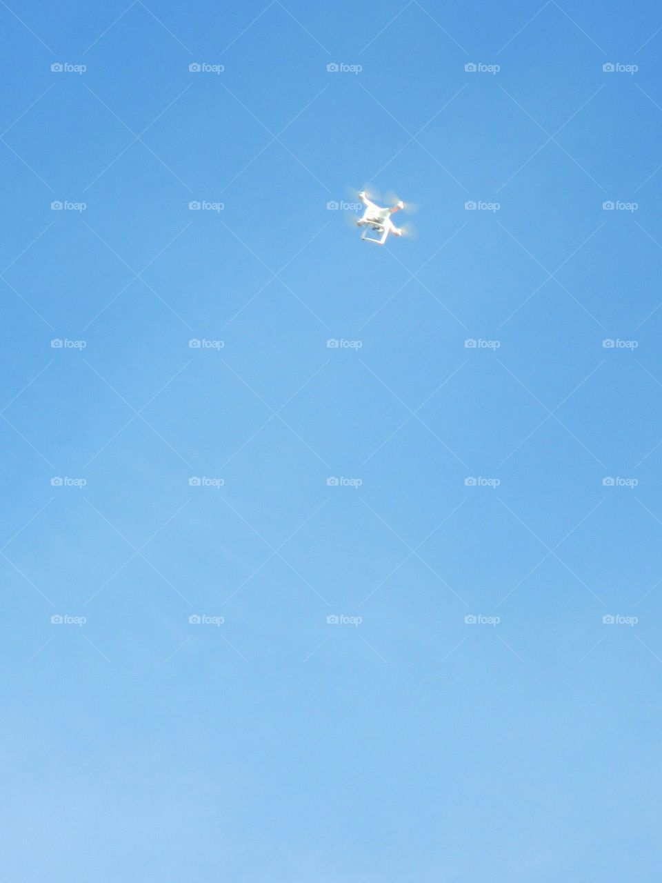 Drone in flight against clear blue sky