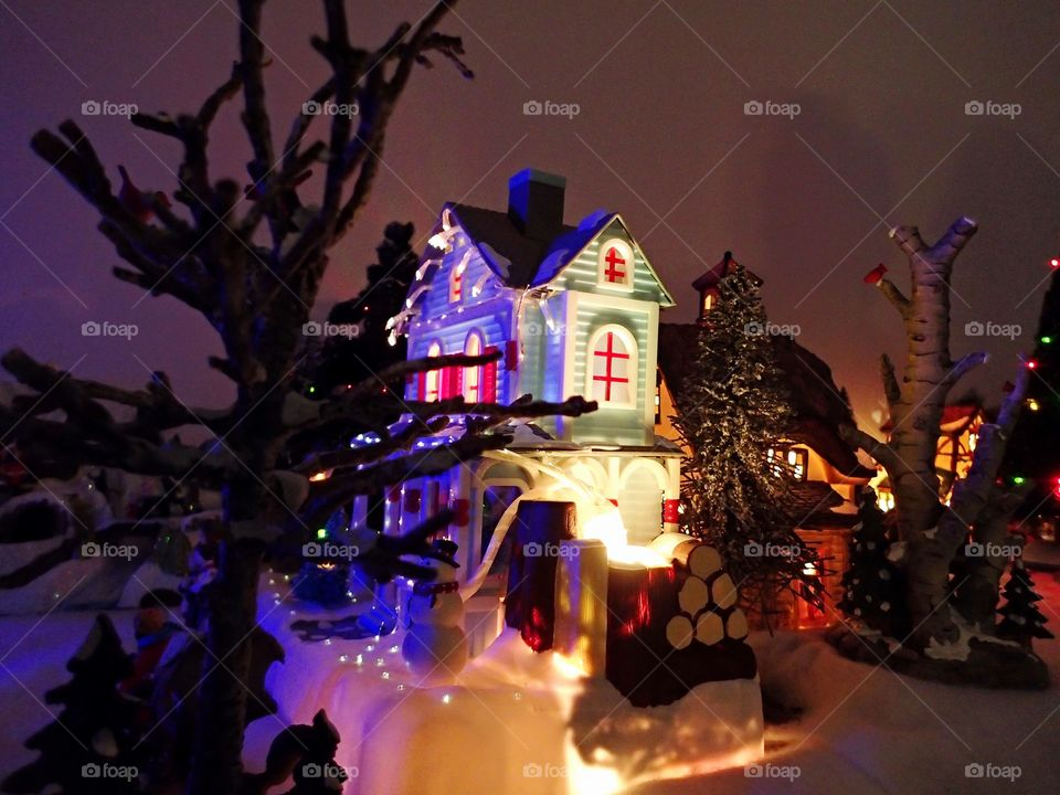 A little house and tree on display in a Christmas village