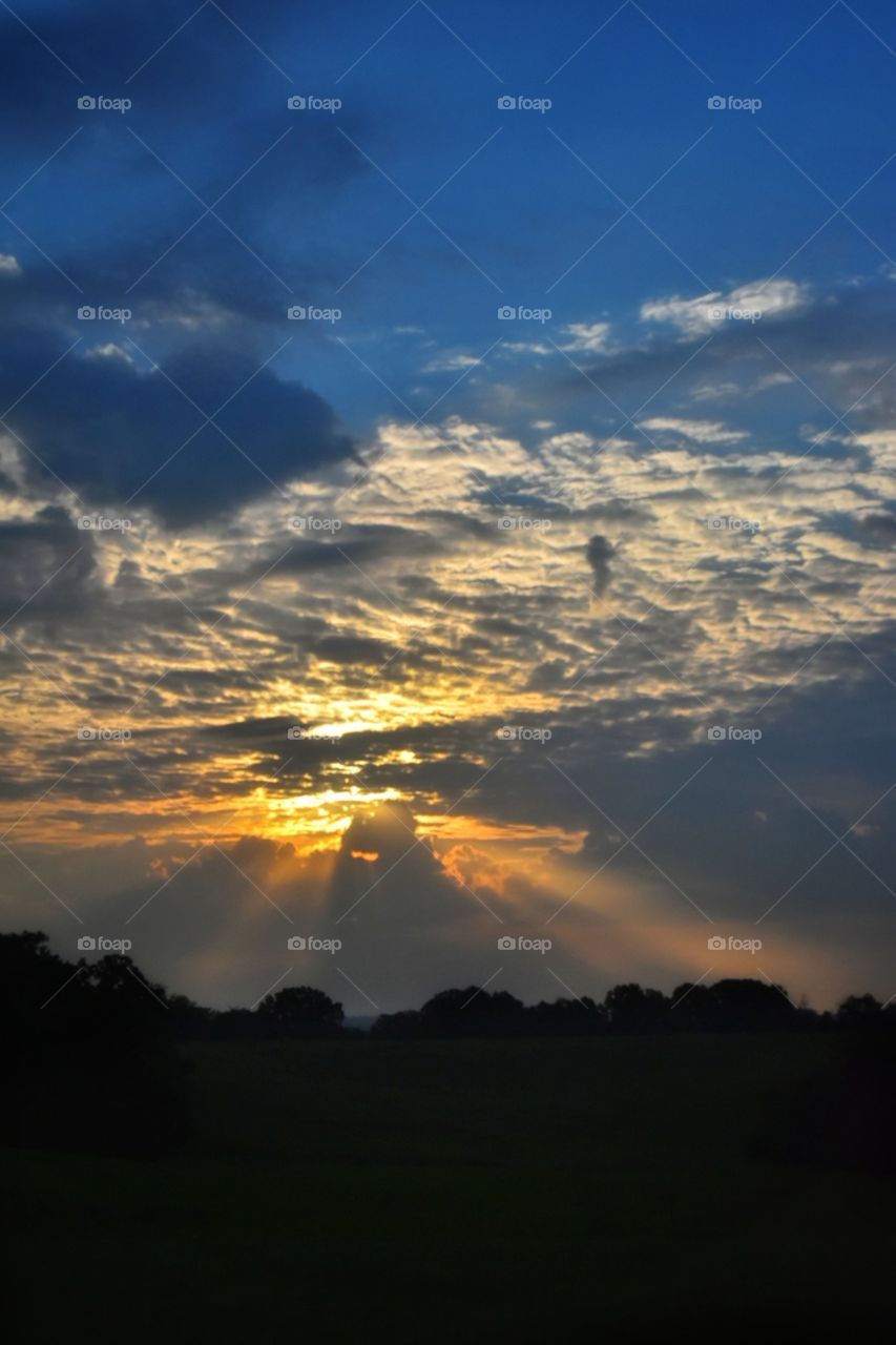 The rays from the setting sun glistening through the clouds