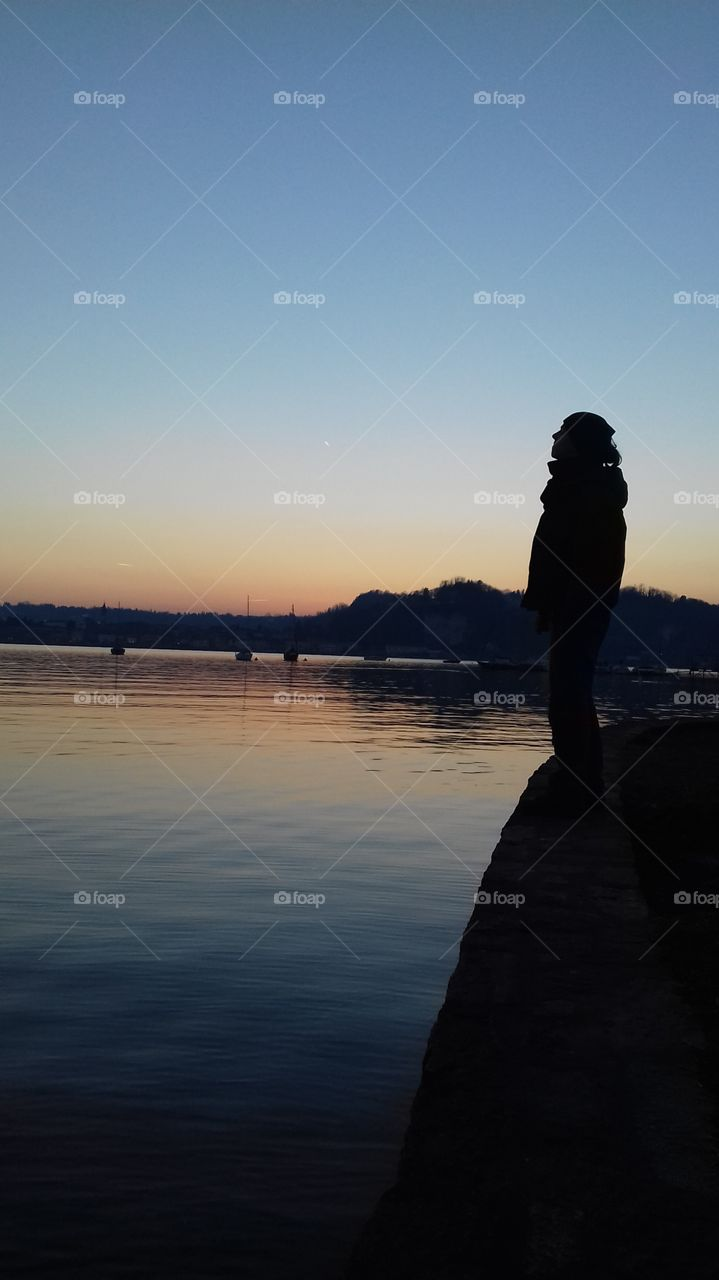 A man profile, lookind at the sky in front of a great italian lake, during the sunset. Water and sky are coloured of blue, red and greed.