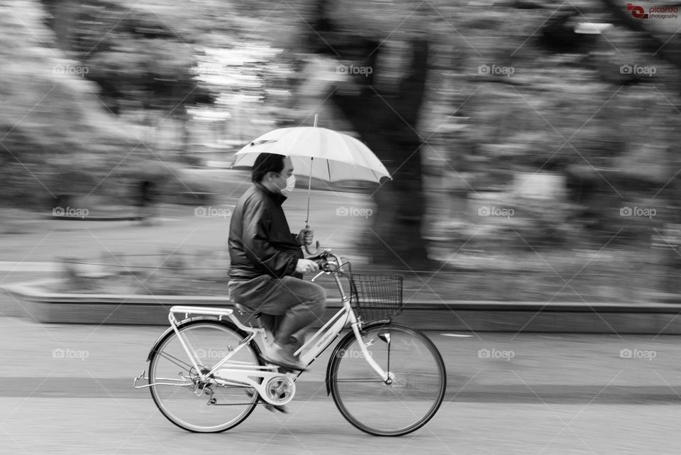 """Bicycle, bicycle!""  A man riding his bike on a rainy day at Ueno Park, Ueno, Tokyo, Japan. Strangely, it is not using a small device attached to the bike's handle that allows you to use an umbrella without using your hands, which is pretty common on japanese's bicycles. Very useful on those rainy days.  http://www.picardo.photography/Portfolio/Street-photography/i-wcmT3HG/A"
