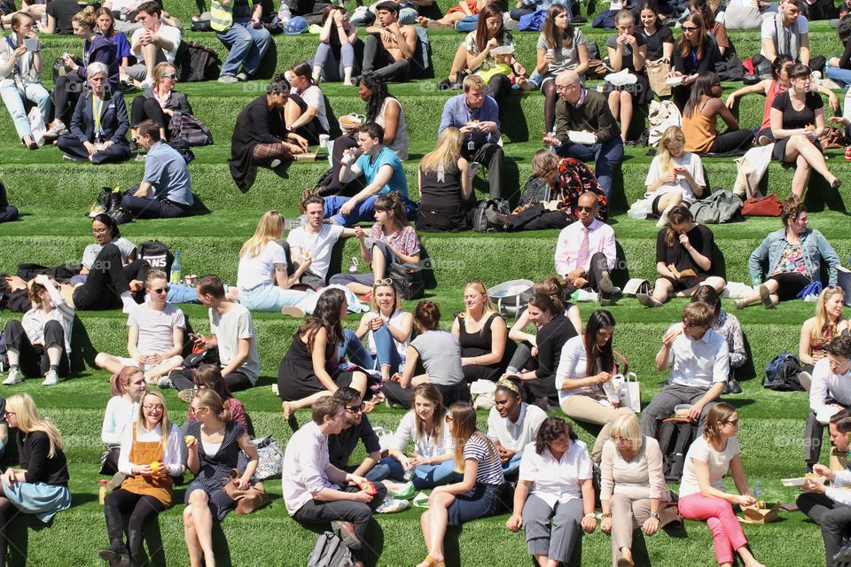 Lots of people enjoying their lunch break in the summer sunshine and relaxing on a grassy hill or bank.