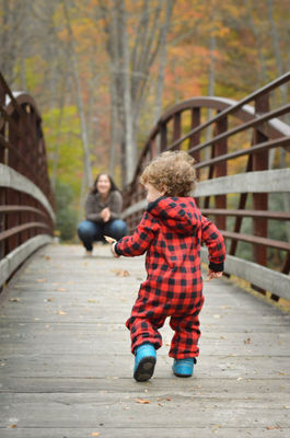 Mother and Son. One-year-old boy running to his mother on a bridge. Photo taken at Mills River in North Carolina.