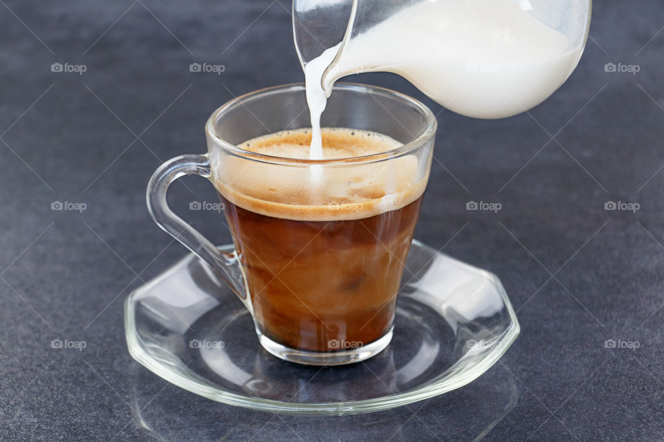 Pouring milk from a jug into a cup of black coffee