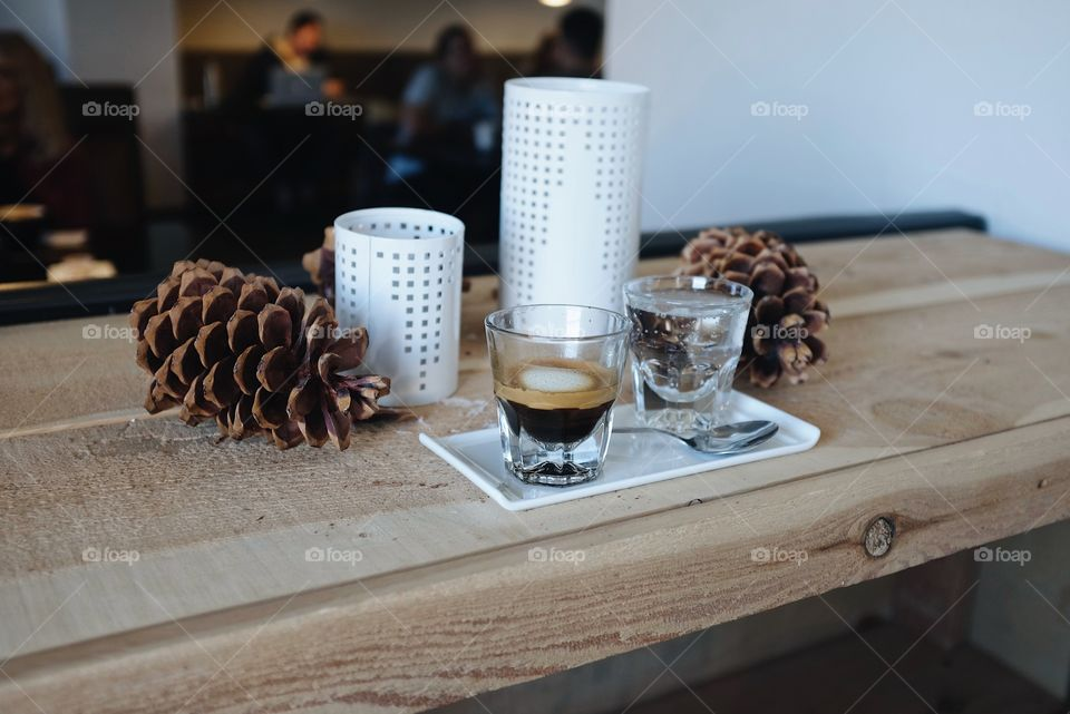 A glass of espresso sitting on a white plate next to a bubbly water in a fall season type theme.