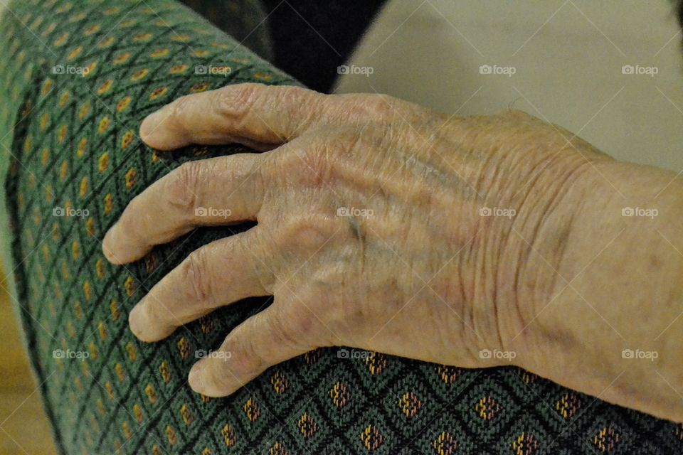 An old womans hand on sofa