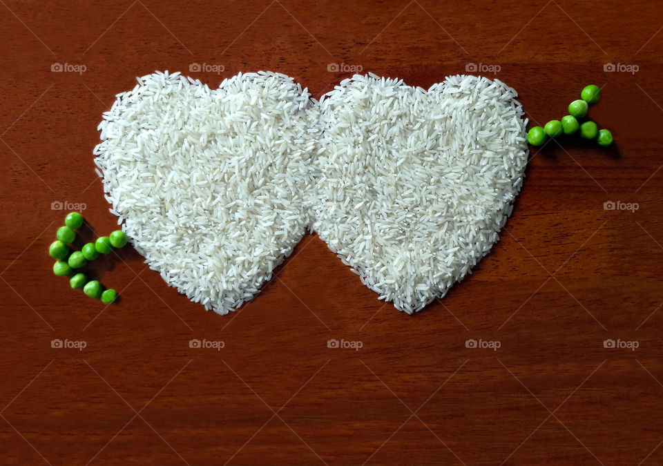 Heart shape of rice with green peas arrow with copy space. Concept of valentine and love card and background.