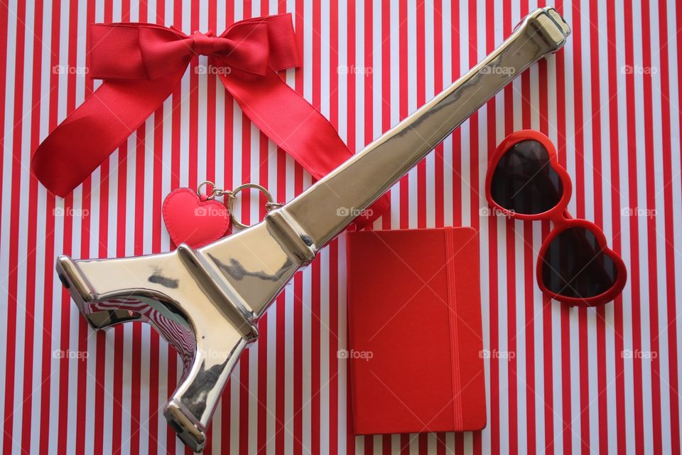 Red and white stripes, Eiffel Tower, heart-shaped sunglasses, notebook, bow and heart-shaped key ring flat lay.