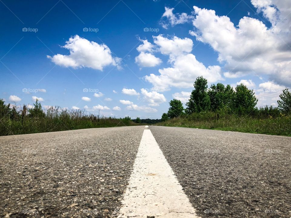 Empty road on a sunny day with blue sky and fluffy clouds