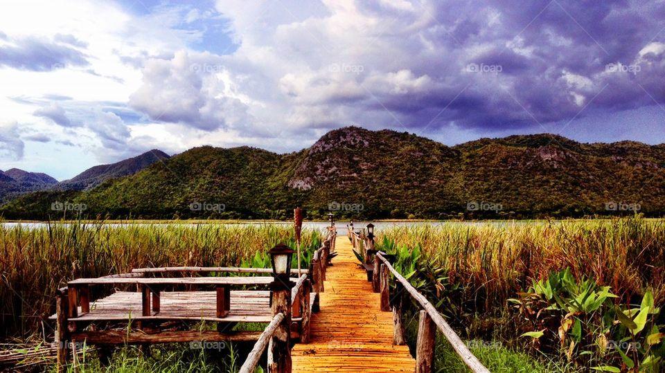 Wooden bridge leading to lake