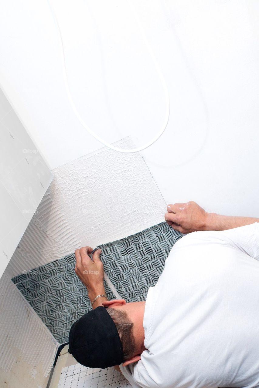 Man setting up mosaic tiles in kitchen