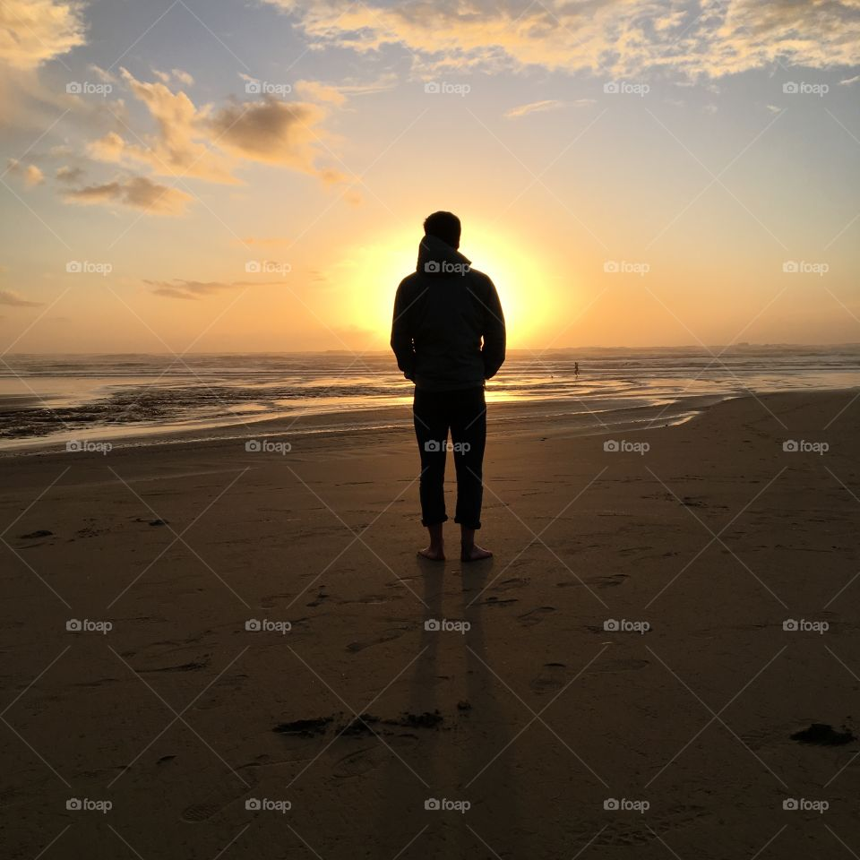 Silhouette of person at sunset by the ocean