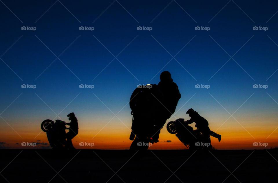 wheelies . the guys doing wheelies at sunrise