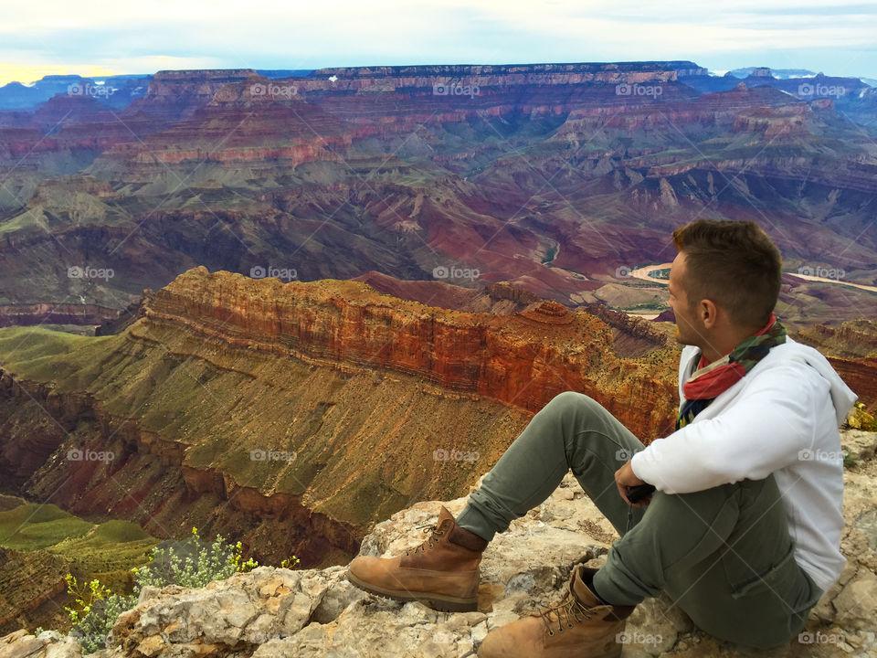 Man sitting on edge of Grand Canyon South rim, Arizona