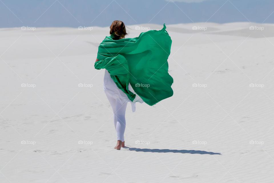Rear view of a women walking on white sand