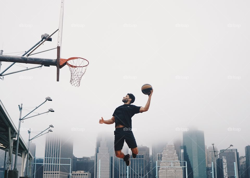 A man playing basketball doing a slam dunk. A city covered in fog is in the background.