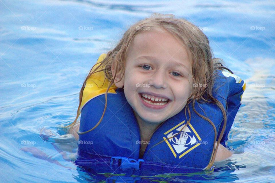Pretty little girl happily swimming in the pool.