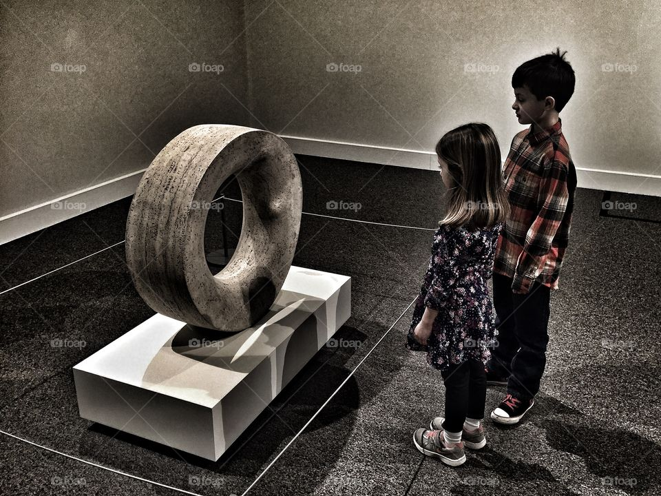 Brother sister looking at concrete tire