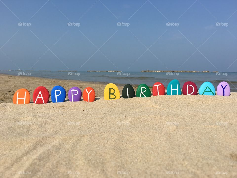 Happy Birthday on colored stones with beach background