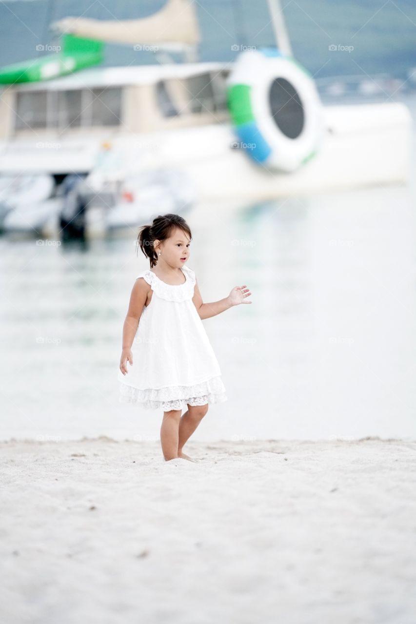 Girl in white dress walking on sand at beach