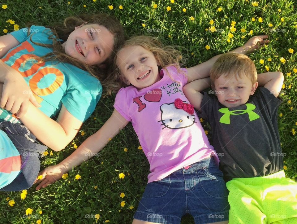 My three beautiful children lounging in a field of buttercups.