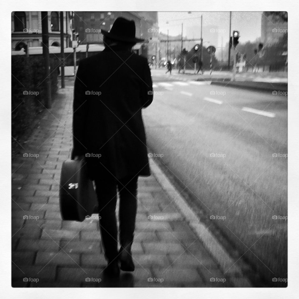 Man with guitar. Black and white documentary photo of an artist with his guitar walking the streets